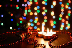 Burning candle on a table with Christmas decorations. On a background garlands Stock Photos