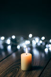 Burning candle on a table with Christmas decorations Stock Image