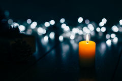 Burning candle on a table with Christmas decorations Stock Images