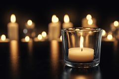 Burning candle on table in darkness, space for text. Funeral symbol stock image