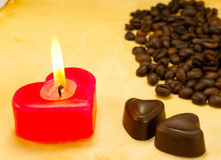 Burning candle, two heart shaped candies and cofee Royalty Free Stock Photo
