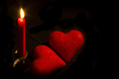 Burning candle with two hearts Stock Photos