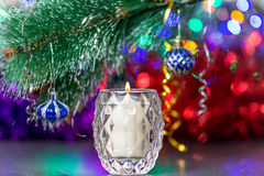 Burning candle under branch of christmas tree with decoration Royalty Free Stock Photography