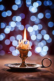 Burning candle in vintage brass candlestick standing on old wood Royalty Free Stock Photos