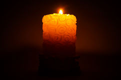 Burning candle. Burning candle with white embossed surface on a black background Stock Photos