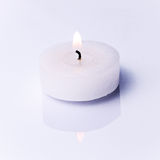 Burning candle. On a white reflective surface Stock Image