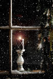 Burning Candle in Window. A burning candle on inside window ledge while snow and snowflakes fall outside, evergreen branches dimly lit on right side of window Stock Image