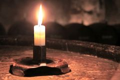 Burning candle in wine cellar Royalty Free Stock Images