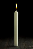 Burning candle on wood against black Royalty Free Stock Photo