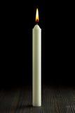 Burning candle on wood against black Royalty Free Stock Photo