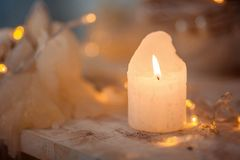 Burning candle on a wooden surface, against the background of Christmas lights. royalty free stock photo