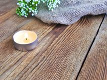 Burning candle on wooden table. stock photo