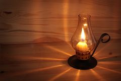 Burning candle it a wooden wall. Royalty Free Stock Photos