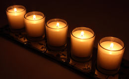 Burning candles. Row of candles burning in glass holders, black background Royalty Free Stock Photography