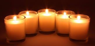 Burning candles. Closeup of five orange burning candles with black background Stock Image