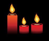 Burning candles. Several lighted candles on a black background Royalty Free Stock Photo