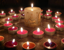 Burning candles. Group of small burning candles and one greater candle Royalty Free Stock Photos