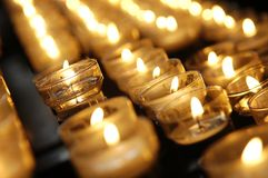 Burning candles. Rows of burning candles inside a curch Stock Photography