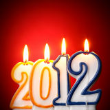 Burning candles. 2012 burning candles close-up over redbackgroumd Royalty Free Stock Image