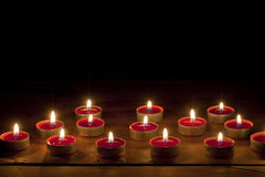 Burning candles. Red candles burning on black background with copy space Stock Image