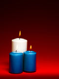 Burning candles. Closeup of a group of three burning candles on red background Royalty Free Stock Photos