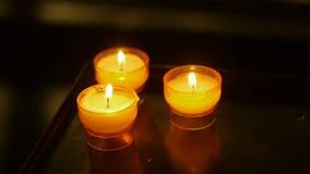 Burning candles in abbey at St Guilhem le Desert, Cevennes France stock video