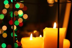 Burning candles against Christmas lights. Burning candles against blurred Christmas lights royalty free stock photos