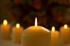 Burning candles against blurred flower background. Line of burning candles with a big candle in the foreground against blurred flower background Stock Images