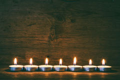 Burning candles on the background of old barn boards Stock Photos