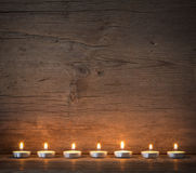 Burning candles on the background of old boards Royalty Free Stock Image