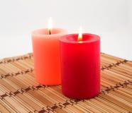 Burning candles on a bamboo napkin. Two burning candles on a bamboo napkin Royalty Free Stock Photography
