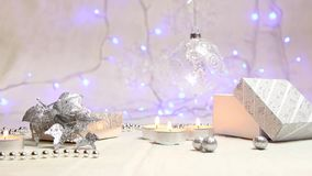 Burning candles, beads, a hanging New Year`s ball and a silver gift box with luminous blue lanterns in the background stock video footage