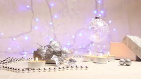 Burning candles, beads, a hanging New Year`s ball and a silver gift box with luminous blue lanterns in the background, a stock video footage