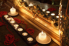 Burning candles and beads lie near mirror Royalty Free Stock Photos