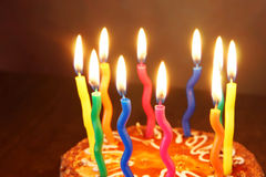 Burning candles on a birthday chocolate cake Stock Photos