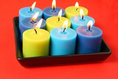 Burning candles in a black holder. Isolated on red background Royalty Free Stock Photography