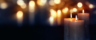 Burning candles in blue darkness with golden lights Royalty Free Stock Photography