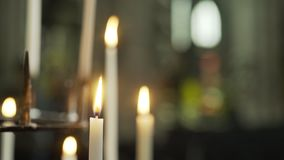 Burning candles at blurred background. Close-up view of many burning candles in candelabrum at blurred background. Unrecognizable Interior of old european stock video
