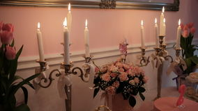 Burning candles, bouquets of flowers on table in banquet hall. Bouquet from miniature pink roses set of lob in stylish candlesticks with ribbons and sweety stock video footage
