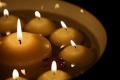 Burning candles in a bowl. A white bowl with numerous burning candles and a flower in water, big candle in the middle Royalty Free Stock Photos
