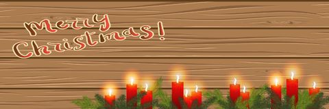 Burning candles in the branches of a Christmas tree, on a wooden. Burning red candles in the branches of a Christmas tree, on a wooden background.  Merry Royalty Free Stock Image