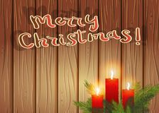 Burning candles in the branches of a Christmas tree, on a wooden. Burning red candles in the branches of a Christmas tree, on a wooden background.  Merry Stock Photo