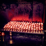Burning candles in Buddhist temple - vintage effect. Royalty Free Stock Image