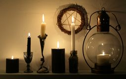 Burning candles in candlesticks, old-fashioned lamp and pentagram stock images