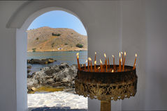 Burning candles in the chapel on the seashore, the wall opening Royalty Free Stock Photo