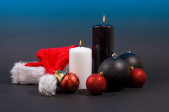 Burning candles with christmas balls and hat Royalty Free Stock Image