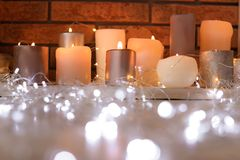 Burning candles and Christmas lights on floor. Indoors stock image