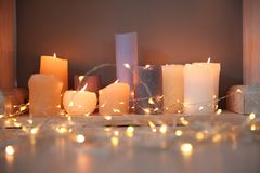 Burning candles and Christmas lights on floor. Indoors royalty free stock photo