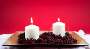 Burning candles for christmas. Lit candles for christmas on red background Royalty Free Stock Photos