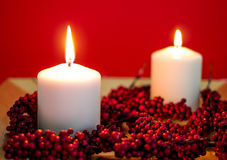 Burning candles for christmas. Lit candles for christmas on red background Royalty Free Stock Photo